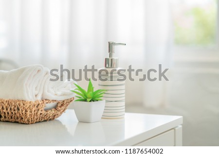 Ceramic soap, shampoo bottles and white cotton towels with green plant on white counter table inside a bright bathroom background #1187654002