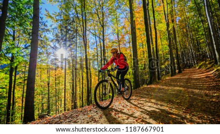 Cycling, mountain biking woman on cycle trail in autumn forest. Mountain biking in autumn landscape forest. Woman cycling MTB flow uphill trail. #1187667901