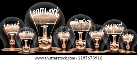 Photo of light bulbs group with shining fibers in a shape of TEAMWORK concept related words isolated on black background #1187673916