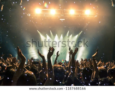 Concert hall with colourful lights and clapping hands #1187688166