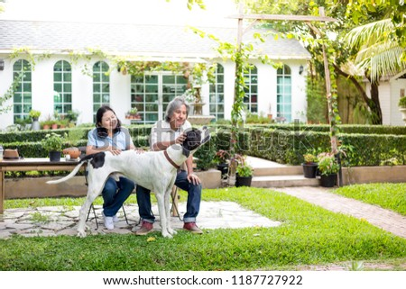 asian senior man and asian senior woman relax with dog in garden, they smiling and feeling happy , retirement lifestyle #1187727922