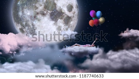 A woman holding on to colored balloons, flying in the sky lying on a cloud. On the sfin a giant moon. Concept of: dreams, freedom. Royalty-Free Stock Photo #1187740633