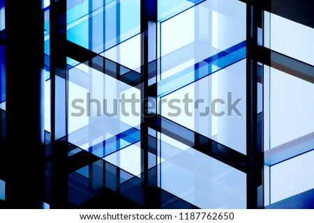 Glass wall with steel or aluminum framework. Structural glazing. Reworked close-up photo of office building fragment in shadows against clear blue sky. Abstract modern architecture background. #1187762650