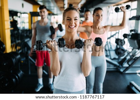 Young woman doing exercise with dumbbell in gym #1187767117