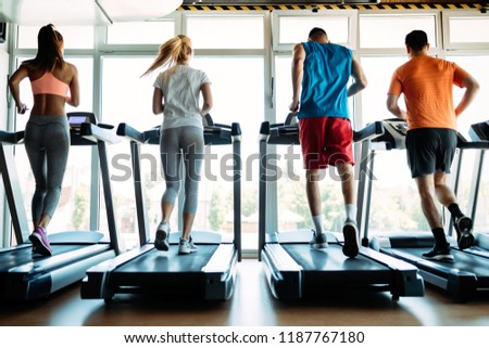 Happy people on treadmills in the gym #1187767180
