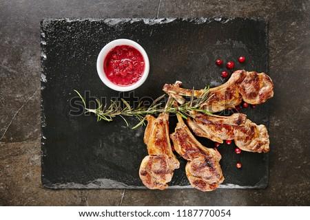 Grilled Lamb Chops with Cranberries and Rosemary on Natural Black Stone Background. Roasted Cutlets on Creative Restaurant Backdrop. Mutton Ribs with Spices and Sause Top View #1187770054