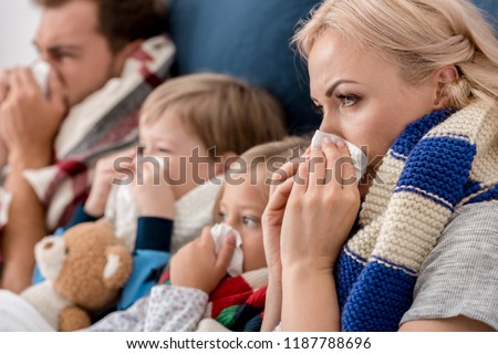 close-up shot of sick young family blowing noses with napkins together while lying in bed Royalty-Free Stock Photo #1187788696