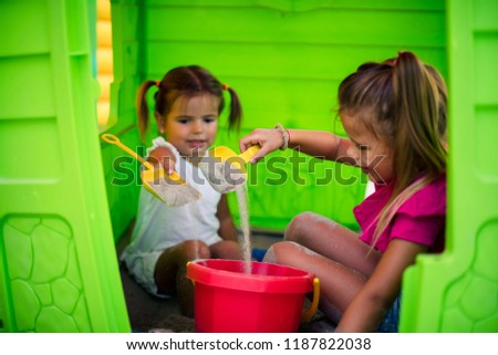 Two friends are playing in the sand on playground. Space for copy. #1187822038