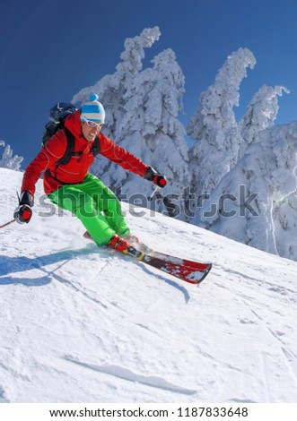 Skier skiing downhill in high mountains against blue sky #1187833648