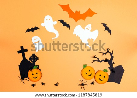 Flat lay Halloween background with cartoon cemetery, pumpkins and ghosts. Space for text.