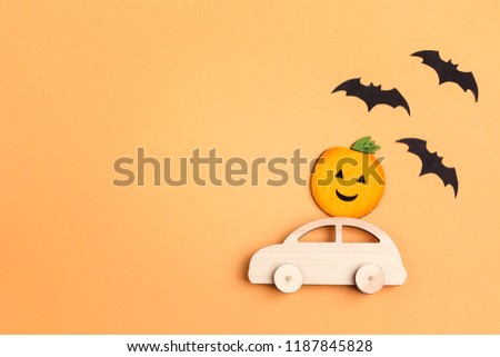 Wooden toy car with funny pumpkin on the roof and bats on orange background. Space for text. Flat lay Halloween background.