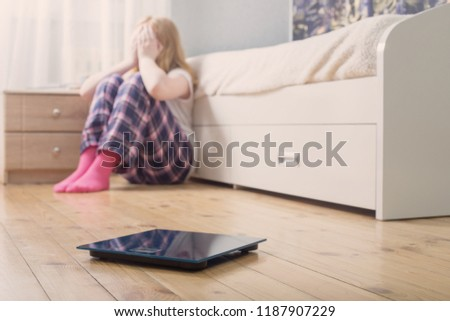 sad teenager girl with scales on floor #1187907229