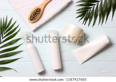 natural hair care products, hairbrush, towel and leaves on a wooden background top view. Shampoo, mask, balm. flatlay Royalty-Free Stock Photo #1187927605