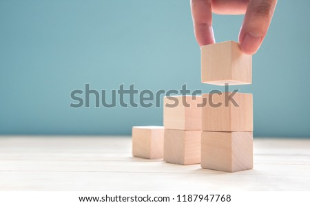 Hand arranging wood cube stacking as step stair. Business concept growth success process on blue background, copy space. #1187947768