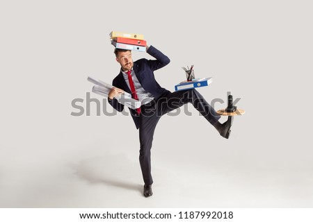 Young businessman in a suit juggling with office supplies in his office, isolated on white background. Conceptual collage with phone, folders. The business, office, work concept. #1187992018