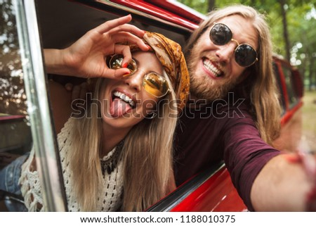Photo of caucasian hippie couple smiling and fooling around while driving retro minivan in forest