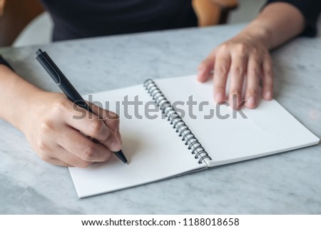 Closeup image of hands writing on blank notebook on the table  #1188018658
