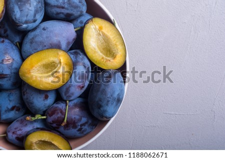 Fresh plums in bowl on wooden table . Fruit background #1188062671