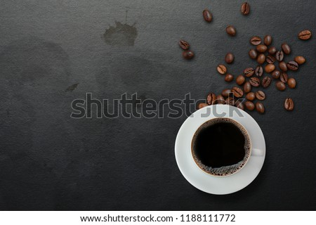 A cup of black coffee with scattered roasted coffee beans on dirty black table with coffee stains background, top view. Americano coffee #1188111772