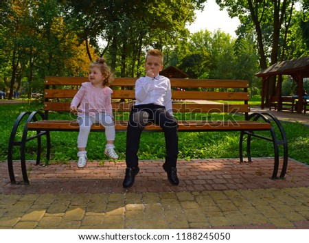 A little boy and a little girl sitting on a bench in the city Park