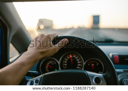 Selective focus man's hand on steering wheel, driving a car at sunset. Travel background #1188287140