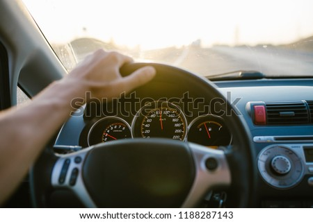 Selective focus man's hand on steering wheel, driving a car at sunset. Travel background #1188287143