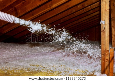 Worker Spraying mineral rock wool of house attic insulation #1188340273