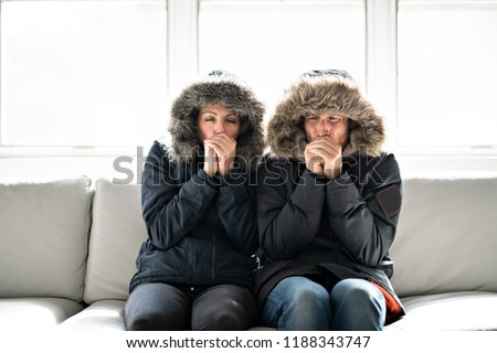 Couple have cold on the sofa at home with winter coat #1188343747