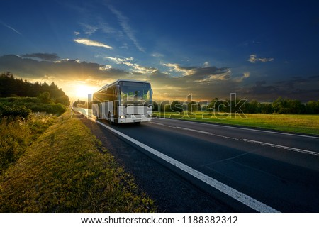 White bus arriving on the asphalt road in rural landscape in the rays of the sunset                                #1188382342