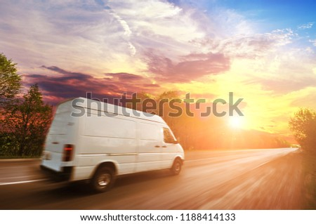 Big white van in motion on the countryside road shipping goods against night sky with sunset #1188414133