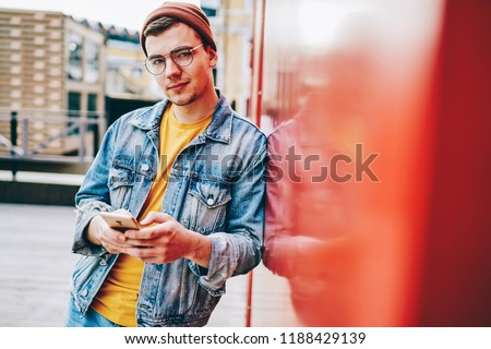 Portrait of caucasian hipster guy in trendy spectacles using mobile phone at urban setting, trendy dressed millennial generation male blogger looking at camera holding smartphone fin hand for chatting #1188429139