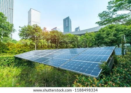 Ecological energy renewable solar panel plant with urban landscape landmarks Royalty-Free Stock Photo #1188498334