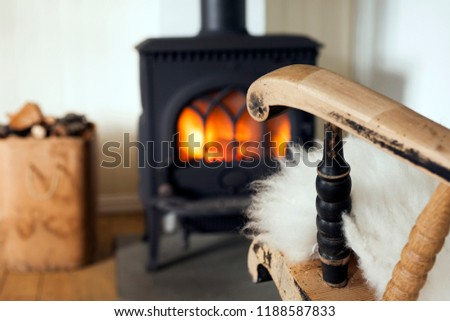 Warm and cozy corner in Scandinavian country house: wood burning stove, box of firewood and old restored rocking chair. Shallow focus on armrest.  #1188587833