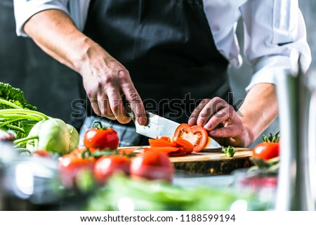 Chef cook preparing vegetables in his kitchen. #1188599194