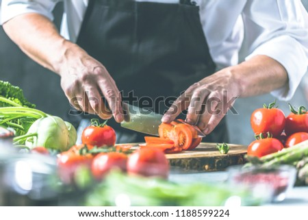 Chef cook preparing vegetables in his kitchen. #1188599224
