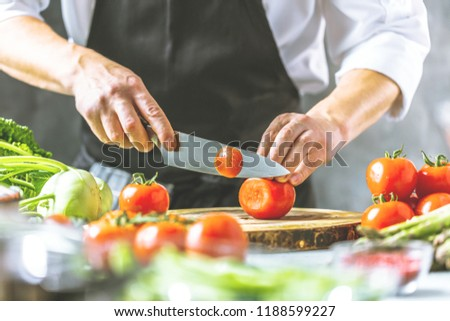 Chef cook preparing vegetables in his kitchen. #1188599227