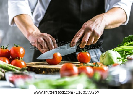 Chef cook preparing vegetables in his kitchen. #1188599269
