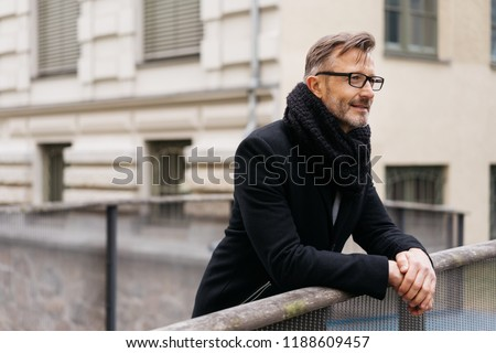 Man in a winter scarf and overcoat standing leaning on a bridge railing over a canal deep in thought staring straight ahead #1188609457