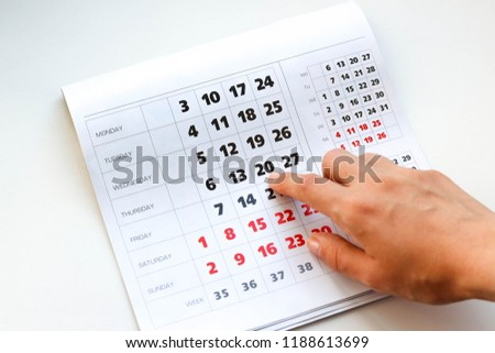 Hand pointing to the calendar. White calendar. Weekends are highlighted in red. Close up #1188613699
