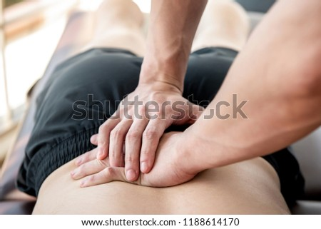Therapist giving lower back sports massage to athlete male patient in clinic #1188614170