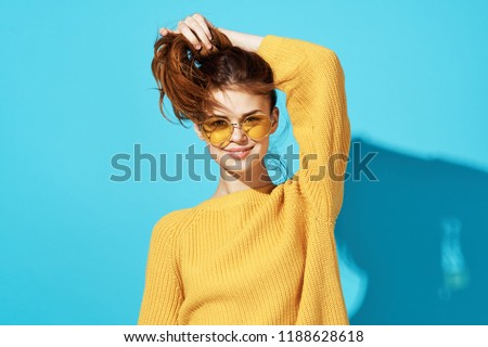 woman in a sweater in yellow glasses raised her hair up                             #1188628618