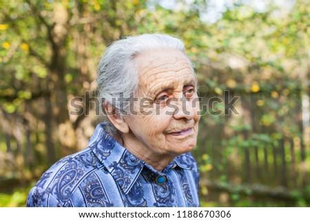 Portrait of old wrinkled lady wearing blue dress, walking in the garden on summertime #1188670306
