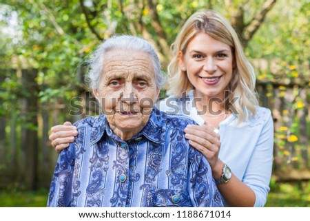 Smiling young caretaker walking with senior lady in the garden #1188671014