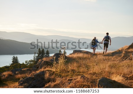 Rear View Of Couple Walking On Top Of Hill On Hike Through Countryside In Lake District UK Royalty-Free Stock Photo #1188687253