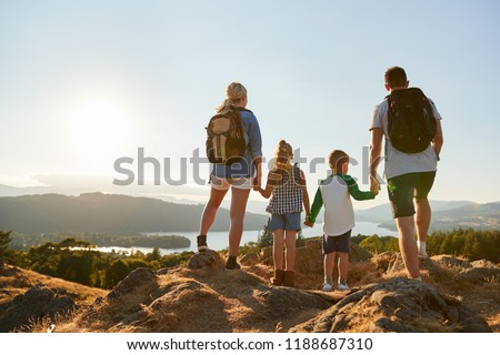 Rear View Of Family Standing At Top Of Hill On Hike Through Countryside In Lake District UK Royalty-Free Stock Photo #1188687310