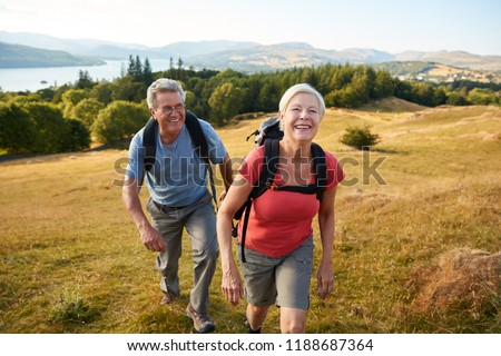 Portrait Of Senior Couple Climbing Hill On Hike Through Countryside In Lake District UK Together #1188687364