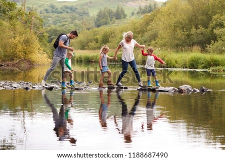 Family Crossing River Whilst Hiking In UK Lake District Royalty-Free Stock Photo #1188687490