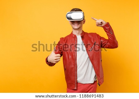 Portrait vogue handsome young man in red leather jacket, t-shirt looking in headset standing isolated on bright trending yellow background. People sincere emotions lifestyle concept. Advertising area #1188691483