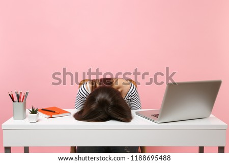 Young frustrated exhausted woman laid her head down on the table sit work at white desk with contemporary pc laptop isolated on pastel pink background. Achievement business career concept. Copy space #1188695488
