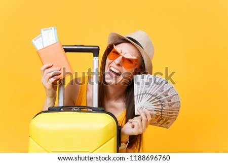 Close up tourist woman in summer casual clothes, hat at suitcase passport cash money isolated on yellow background. Passenger traveling abroad to travel on weekends getaway. Air flight concept #1188696760